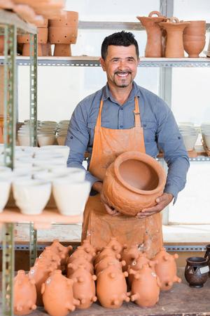 Happy male sculptor having ceramics in hands and standing in workroom Stock Photo