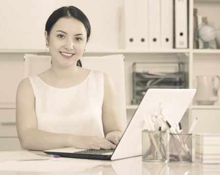 expertize: Young woman manager working on interesting project in office