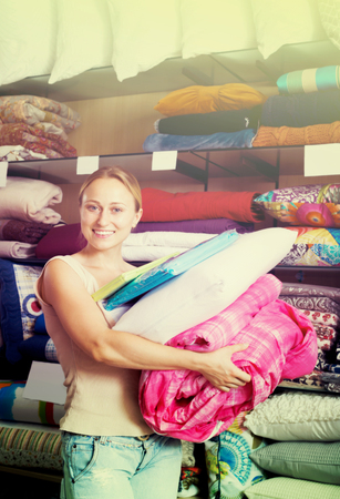 bedspread: Portrait of woman choosing blanket, pillow and textile in bedding section in shop