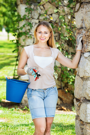 Happy smiling young  woman having horticultural instruments in garden on summer day