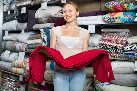 bedspread: Young happy smiling positive woman buying bed spread in home textile store
