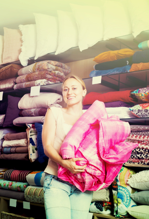 bedspread: Laughing woman choosing blanket in bedding section in shop