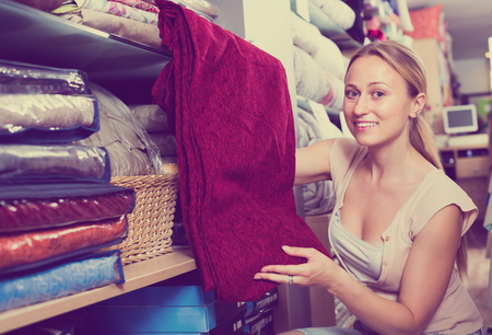 bedspread: cheerful young woman customer selecting comfortable bed cover in textile department