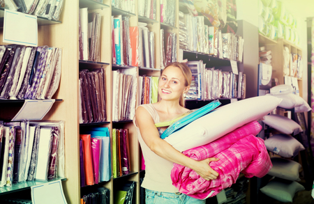 bedspread: smiling young woman customer picking bed cover, pillow, bedding set in textile department