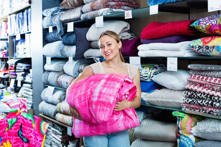 bedspread: Young  glad woman buying bed spread in home textile store Stock Photo