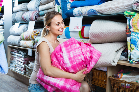 bedspread: Young cheerful smiling  woman buying bed spread in home textile store