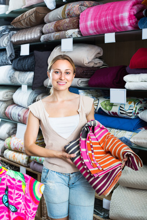 bedspread: happy woman customer picking bed cover in textile department