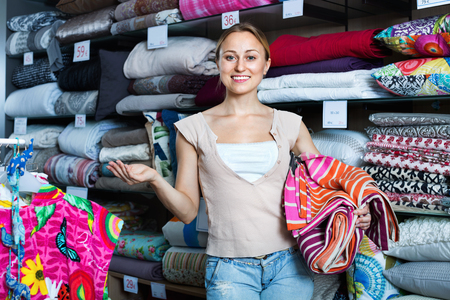 bedspread: Young smiling positive woman buying bed spread in home textile store