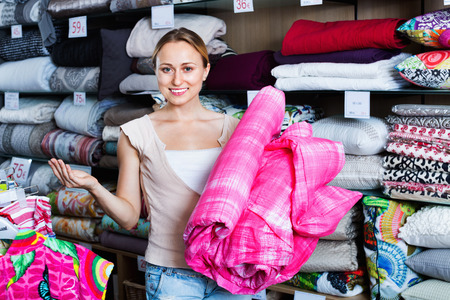 bedspread: Cheerful smiling glad woman buying bed spread in home textile store Stock Photo