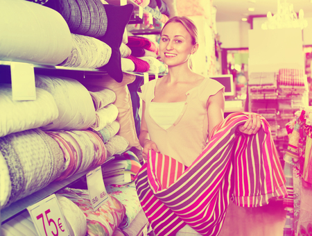bedspread: Young happy positive woman buying bed spread in home textile store Stock Photo