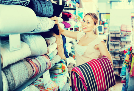 bedspread: Happy smiling positive woman buying bed spread in home textile store
