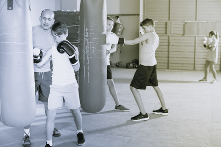 combination: Adult boxing instructor and smiling children practicing blows on boxing bag