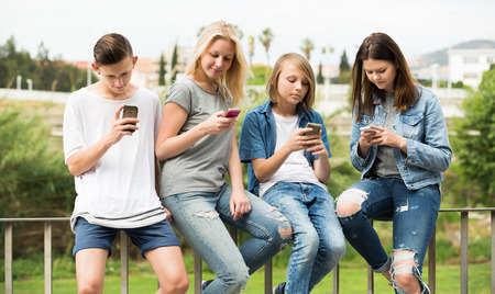 Young two girls and two boys playing with mobile phones outdoors Imagens