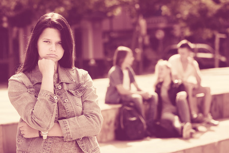 Offended teenage girl standing away from friends feeling depressed
