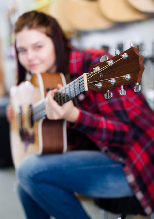 Girl is deciding on acoustic guitar in guitar shop. Stock Photo