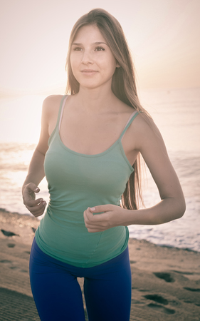 Female in blue T-shirt is jogging on the beach.