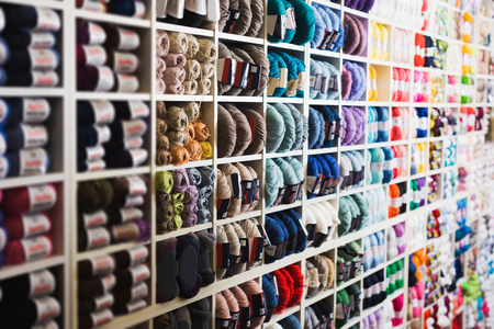 Shelves with beauty wool and yarn in knitting shop Stock Photo