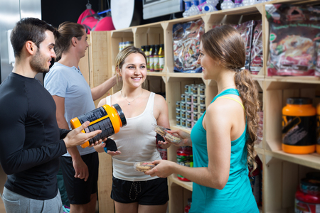 Portrait of smiling active people with sport nutrition products in shop