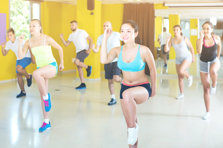 Enthusiastic people performing modern dance in fitness studio