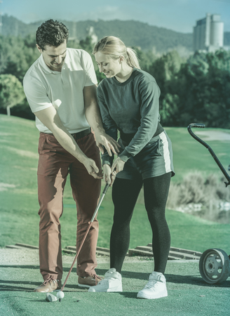 brassy: Cheerful male golf trainer showing female player how to hit ball rightly