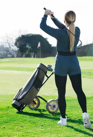 Young female golfer made successful hit at golf course