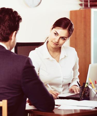 銀行スペイン語エージェント顧客に耳を傾け、代理店に笑みを浮かべて