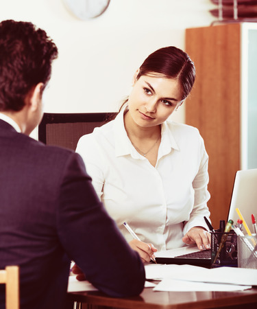 Banking spanish agent listening to customer and smiling in agency