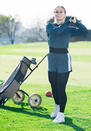 happy american  woman golfer propelled ball successfully at golf course