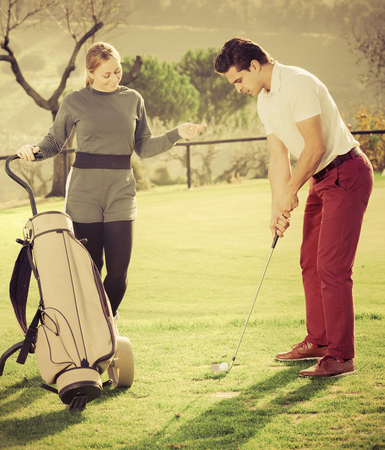 brassy: Glad golf partners playing tour of golf at golf course together Stock Photo