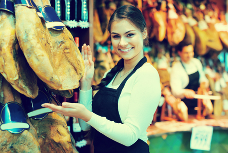 Smiling young woman  in apron offering tasty jamon for customers in shop Stock Photo