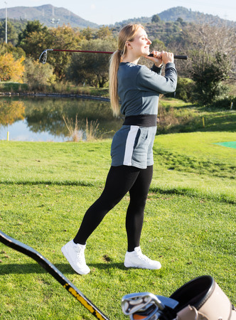 brassy: Glad female golfer made successful hit at golf course Stock Photo