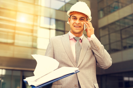 Smiling businessman holding papers and having phone call conversation outdoor Stock Photo