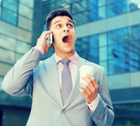 Surprised businessman talking on phone outdoors with disposable cup in hand Stock Photo