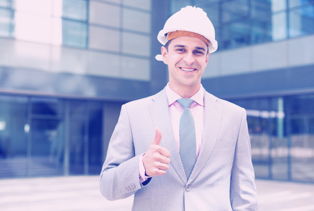 Businessman in hardhat showing thumb as sign of job well done