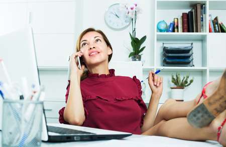 Smiling business woman chatting on phone holding legs on desk at office
