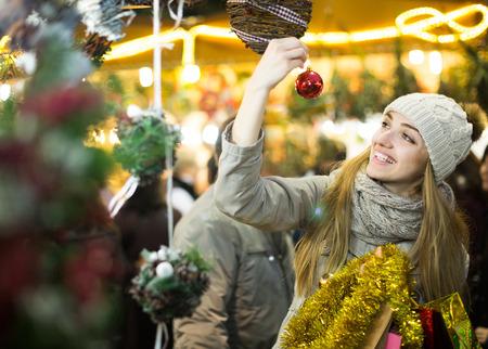 Portrait of happy european smiling woman in coat posing at Xmas fair in evening Stock Photo