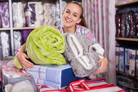 boasting: Young female shopper buying multiple items in textile shop