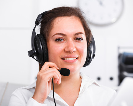expertize: Smiling woman worker working effectively at call-center Stock Photo