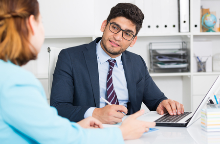 Successful businessman in glasses talking to female colleague in office Stock Photo