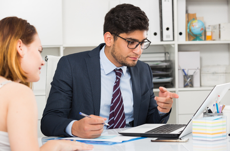 Positive businessman welcoming female client at workplace in office