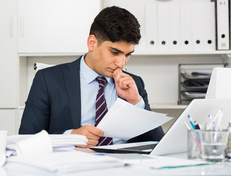 selling service: Male professional is reading documents about the transaction in office.