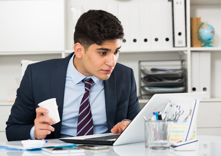 expertize: Young man is working at a computer and drinking coffee in the office. Stock Photo