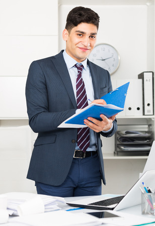 selling service: Man is signing agreement papers of financial nature at office.