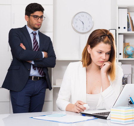 tardiness: Upset woman sitting at laptop in office with disgruntled boss behind