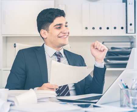 selling service: Smiling offece worker reading documents about the transaction in office. Stock Photo