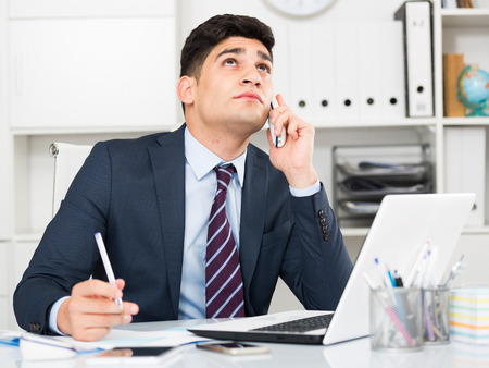expertize: Young manager is discussing the contract by phone in the office.