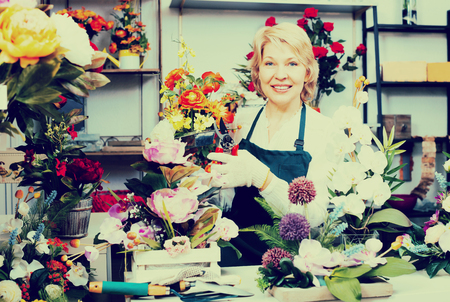 selling service: Smiling mature woman florist in apron holding scissors and fixing flowers in gardening counter Stock Photo