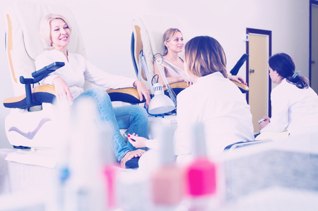 senior Female clients doing toenails in nail salon in afternoon Stock Photo