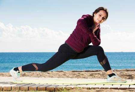 Positive young woman doing yoga asanas and pranayama at seaside