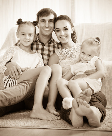 Family values: portrait of happy mom and dad with little girls indoors